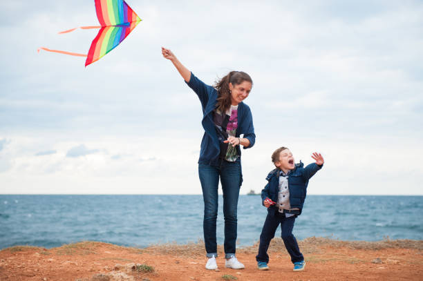 foster parent and child flying kite on beach ireland