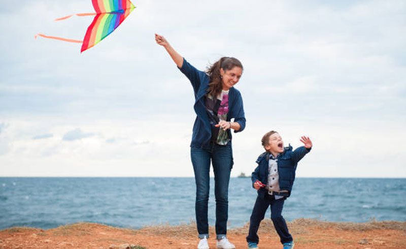 foster parent and young person child playing kite beach